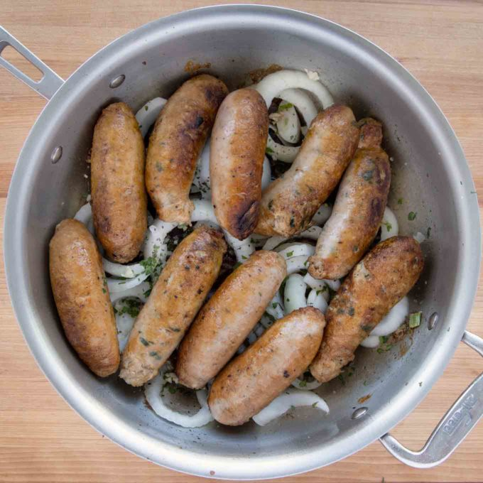sausages added back into the pan on top of the onions