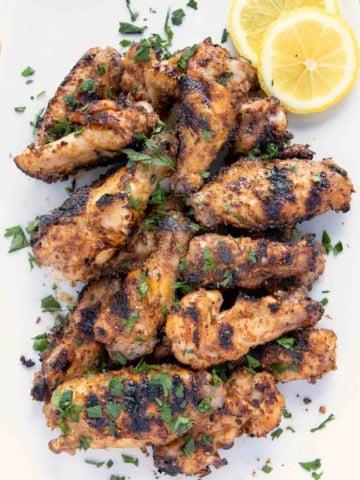 overhead shot of grilled dry rub lemon pepper chicken wings on a white platter