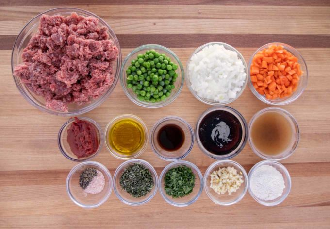 Ingredients to make Cottage Pie in glass bowls on a cutting board