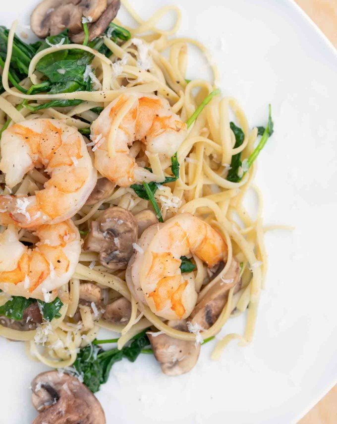 garlic shrimp with mushrooms and spinach served over linguine on a white plate