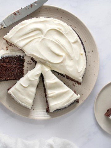 overhead shot of Guinness chocolate cake sliced on a white platter with a slice on a small plate