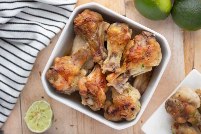Tequila Lime Drunken Chicken Wings on a white bowl next to a kitchen towel