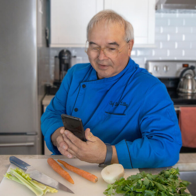 chef dennis sitting at his kitchen counter holding a cell phone