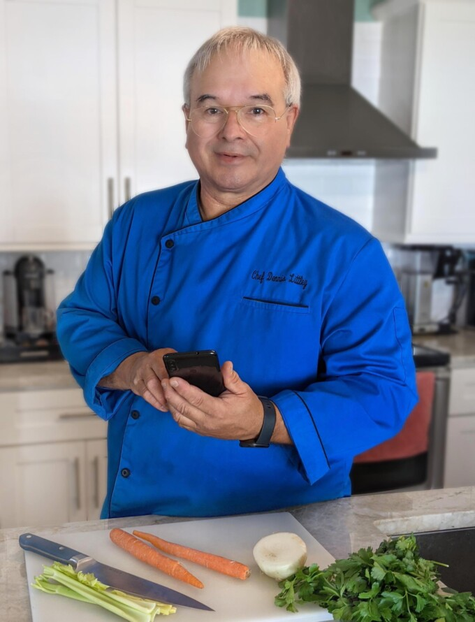 chef dennis in his kitchen holding a phone and smiling
