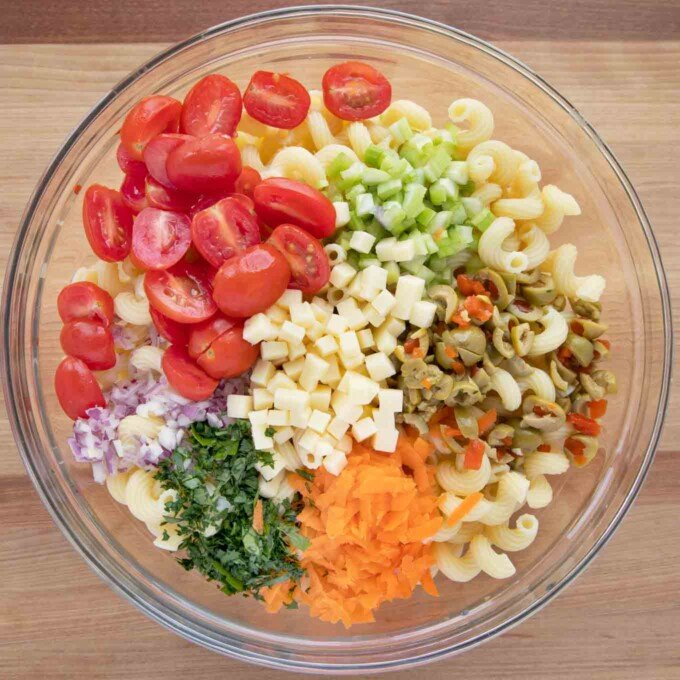 vegetables, olives and cheese added to the bowl of cooked macaroni