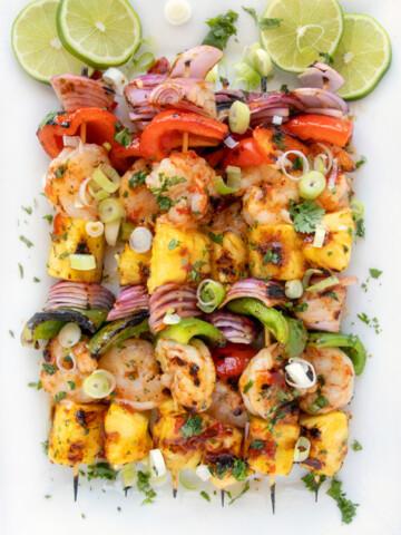 Grilled Shrimp and pineapple skewers on a white platter