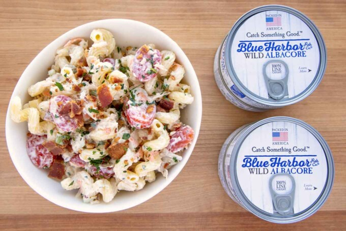 white bowl of tuna macaroni salad with cans of tuna next to it