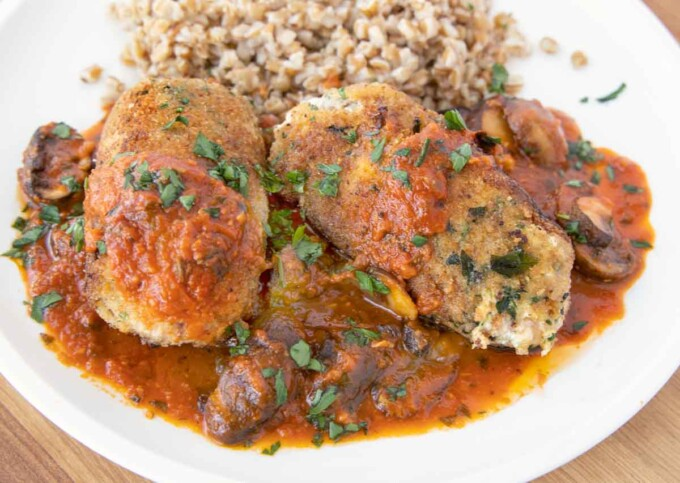 two beef braciole with mushroom tomato sauce and farro on a white plate