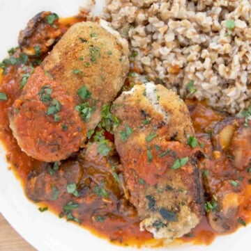 overhead shot of two beef braciole with mushroom tomato sauce and farro on a white plate