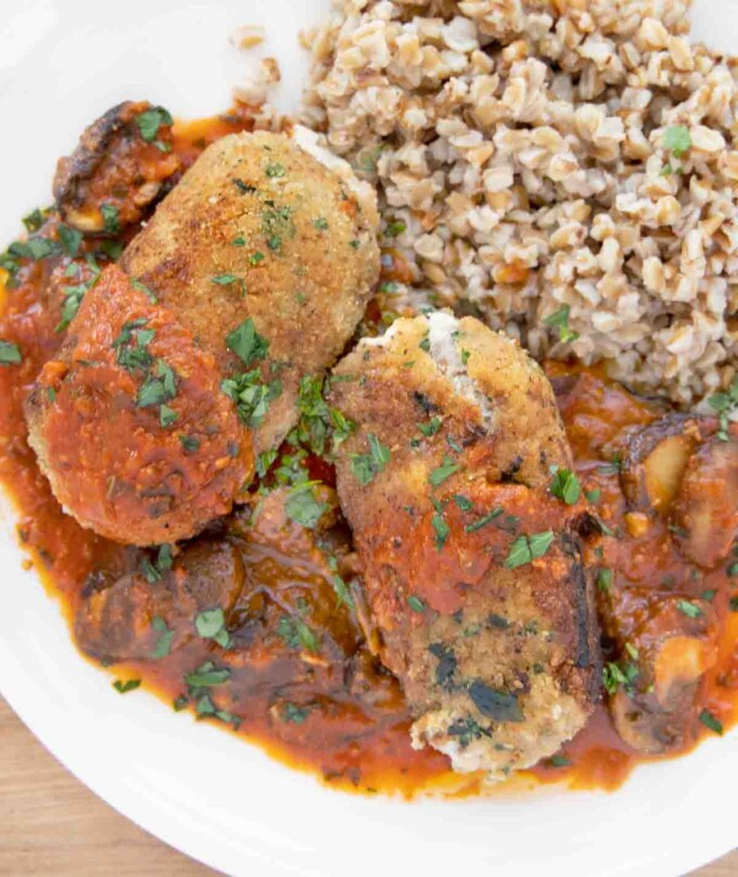 overhead shot of beef braciole with mushroom tomato sauce and farro on a white plate