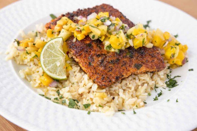 pan seared seasoned salmon with mango salsa on a bed of rice on a white plate
