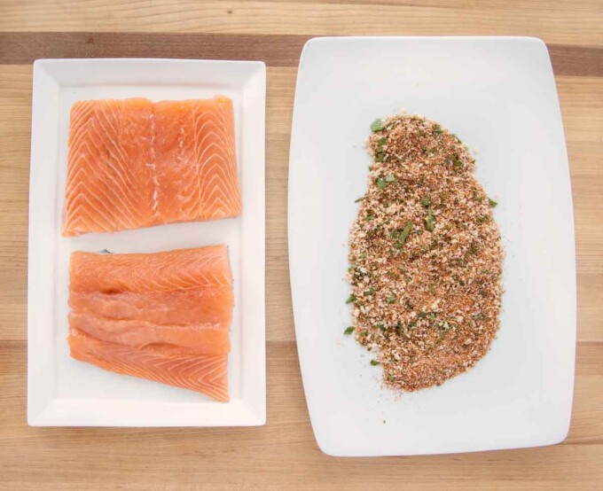 2 salmon fillets on a white platter next to another platter with the seasoning blend