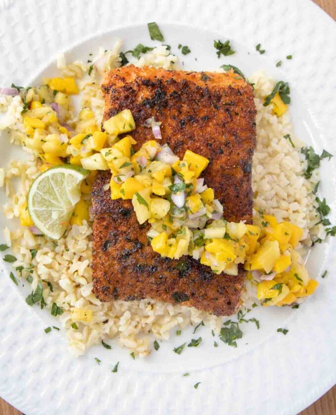 overhead view of pan seared seasoned salmon with mango salsa on a bed of rice on a white plate