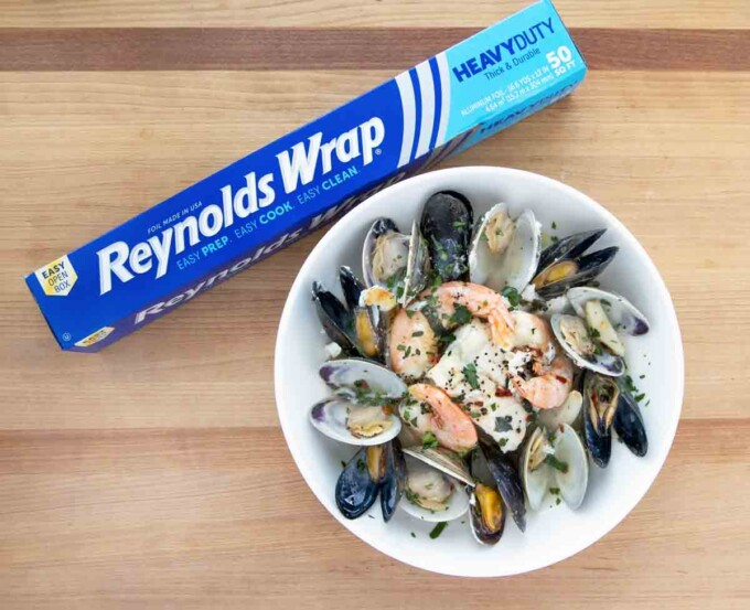 seafood combo in white bowl with roll of reynolds foil