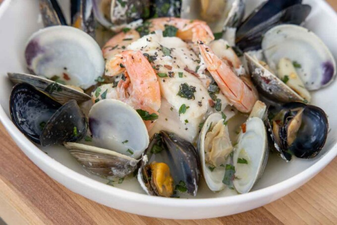 close up of seafood combo in white bowl