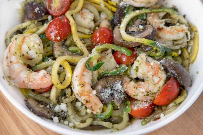 close up of shrimp and zoodles in a white bowl