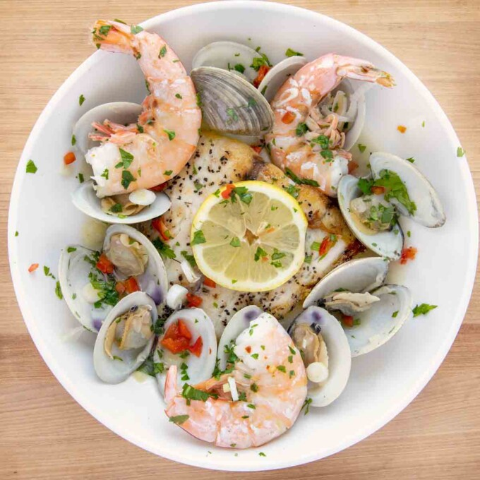 overhead view of a white bowl of barramundi with clams and shrimp