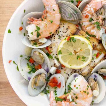 overhead partial view of a white bowl of barramundi with clams and shrimp