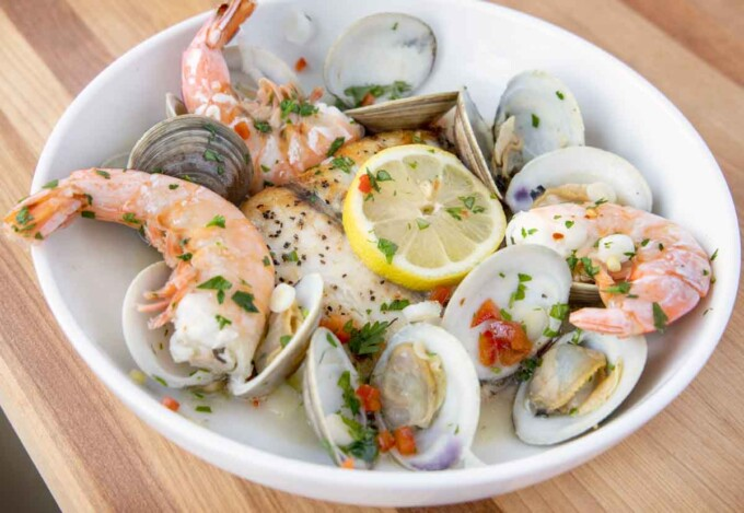 close up of pan seared barramundi with clams and shrimp in a white bowl