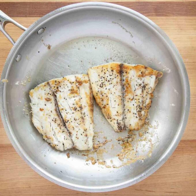 seared seasoned barramundi in a saute pan