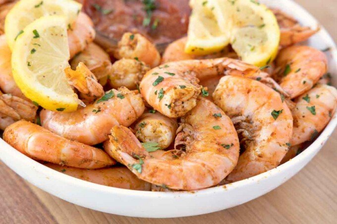 peel and eat shrimp in a white bowl with lemons