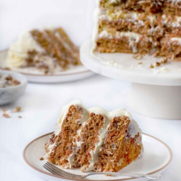 slice of carrot cake on a plate with a fork with an other slice and the remainder of the whole cake on a pedestal in the background