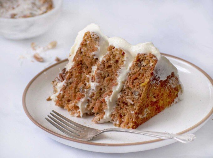 slice of carrot cake on a white plate with a fork