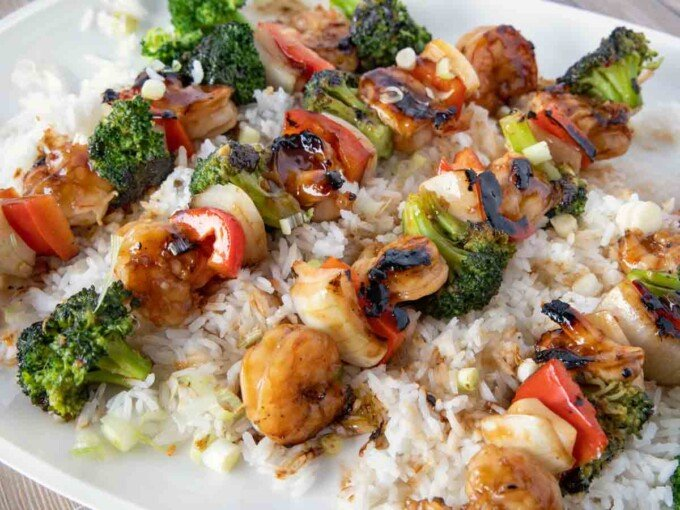 close up of shrimp and broccoli skewers on a bed of jasmin rice