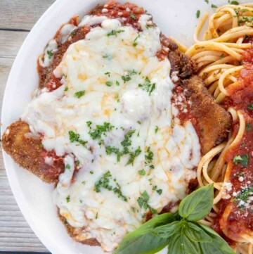 overhead shot of eggplant parm with linguine on a white plate