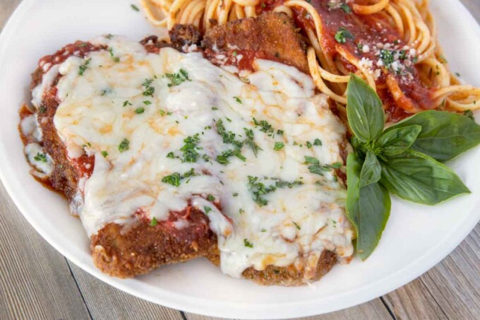 close up of eggplant parm with a side of linguine on a white plate with a sprig of basil