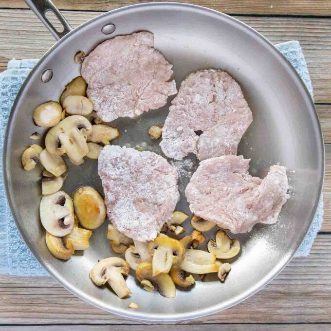 floured veal medallions being added to a pan with sauteed mushrooms