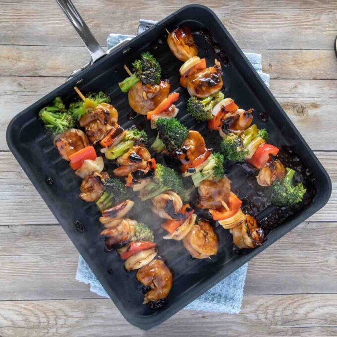 shrimp and broccoli skewers on a square black grill pan