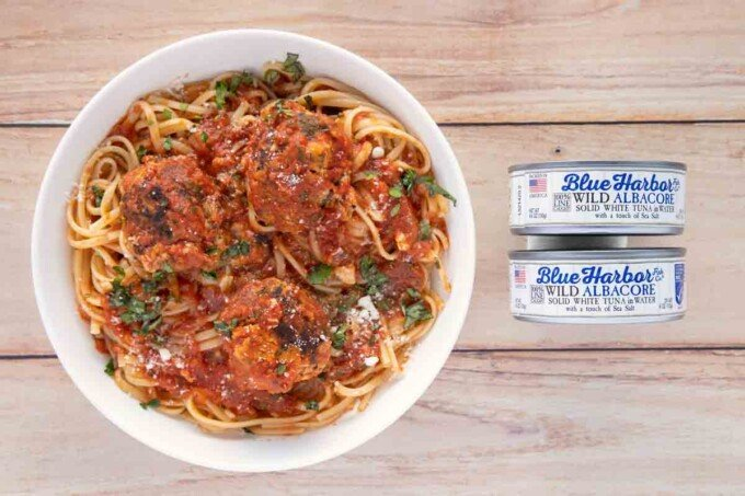 overhead view of tuna meatballs and linguine in a white bowl next to two cans of blue harbor tuna