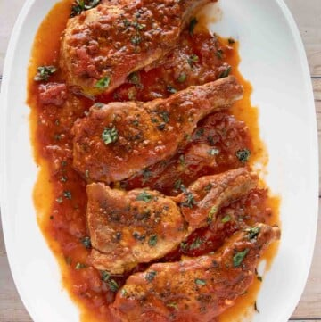overhead view of four Sicilian pork chops on a white platter