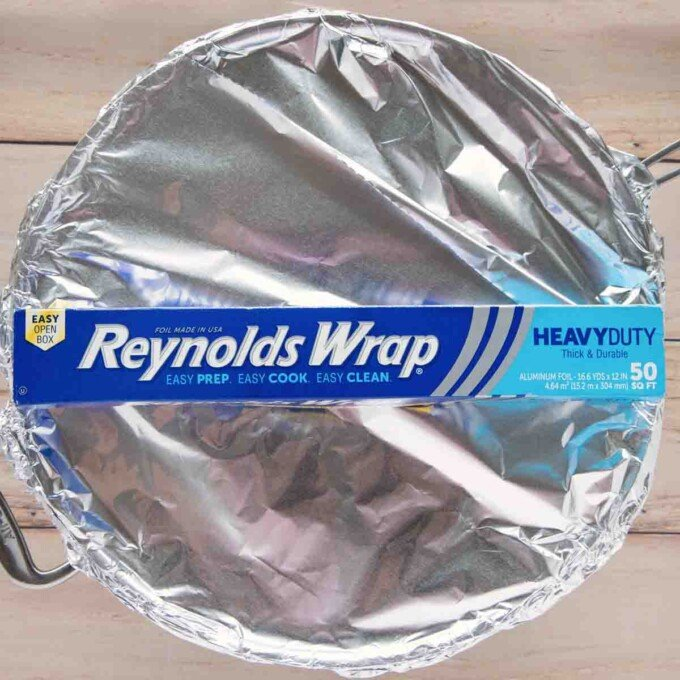 large skillet with pork chops covered in foil with a box of Reynolds wrap foil on top of the pot