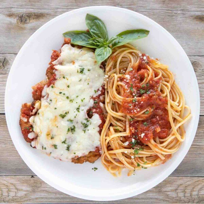 overhead view of veal parm and linguine white plate