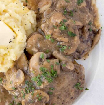 overhead view of salisbury steak with mashed potatoes on a white plate