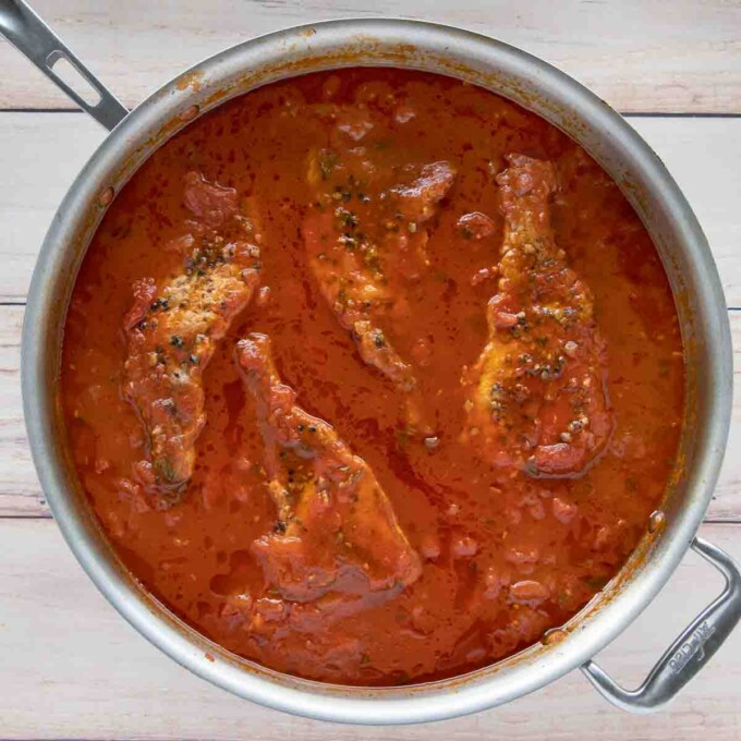 large skillet with fully cooked pork chops in the spicy marinara