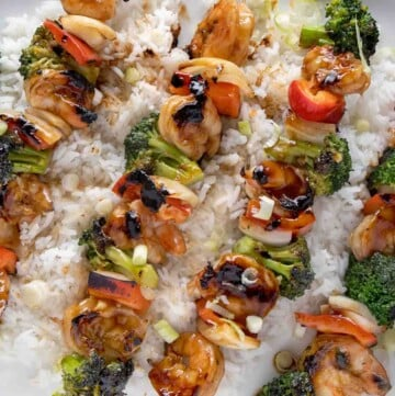 shrimp and broccoli skewers on a bed of jasmin rice on a white platter