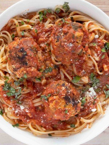 overhead view of tuna meatballs and linguine in a white bowl