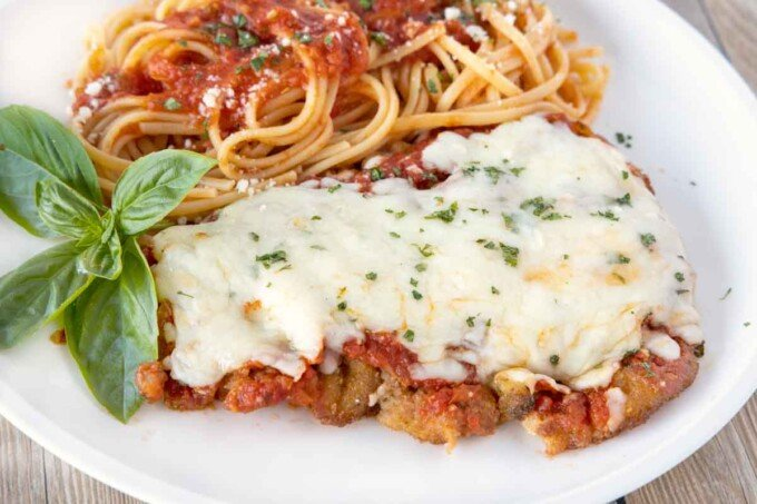 close up side view of veal parm and linguine on a white plate