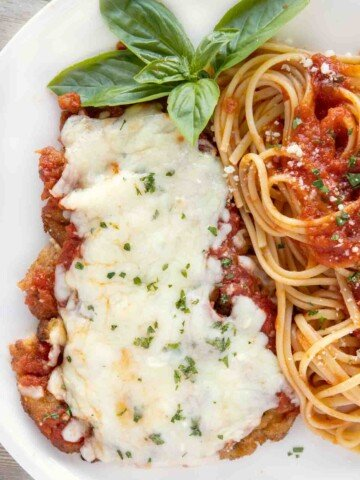 overhead view of veal parm and linguine on a white plate